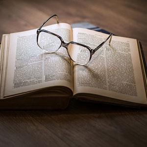 開いたページに眼鏡が置かれている本