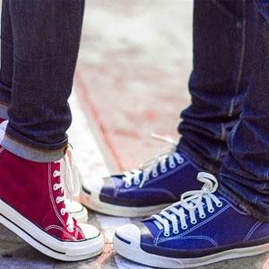 背伸びをしている女性と向かい合っている男性の足元