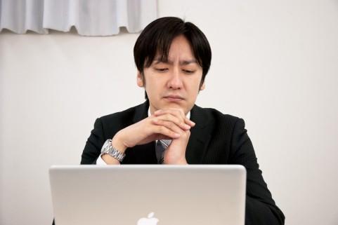 パソコンを見て悩んでいる男性