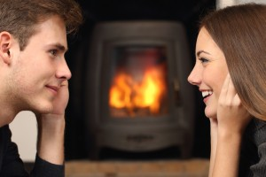 暖炉の前で雑談するカップル