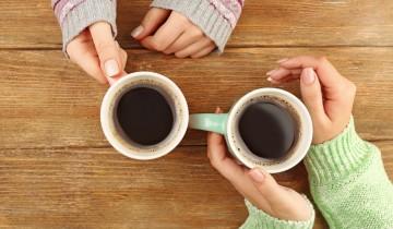 カップルの腕と二つのコーヒー