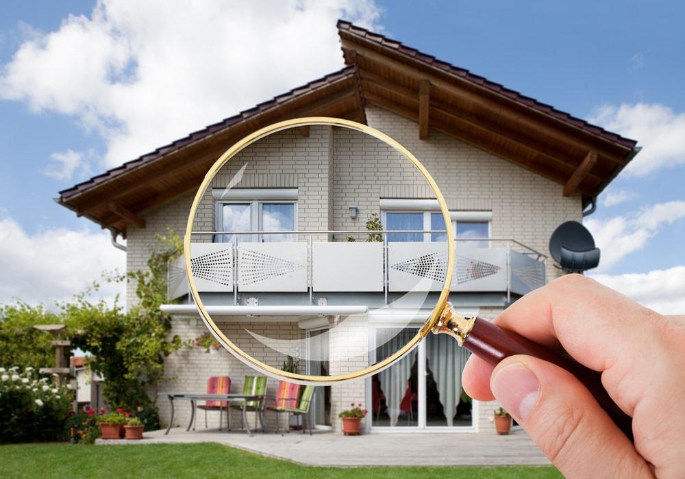 虫眼鏡で家を見ている