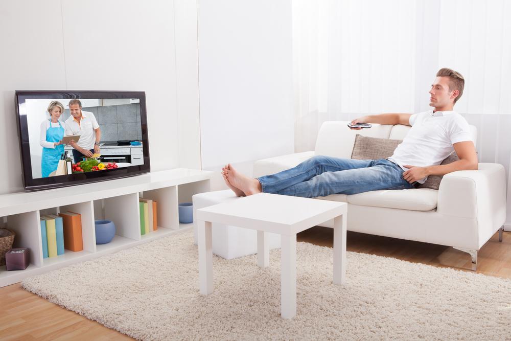 男性がソファに座ってテレビを見ている