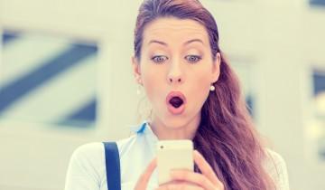 スマートフォンを見て驚いている女性