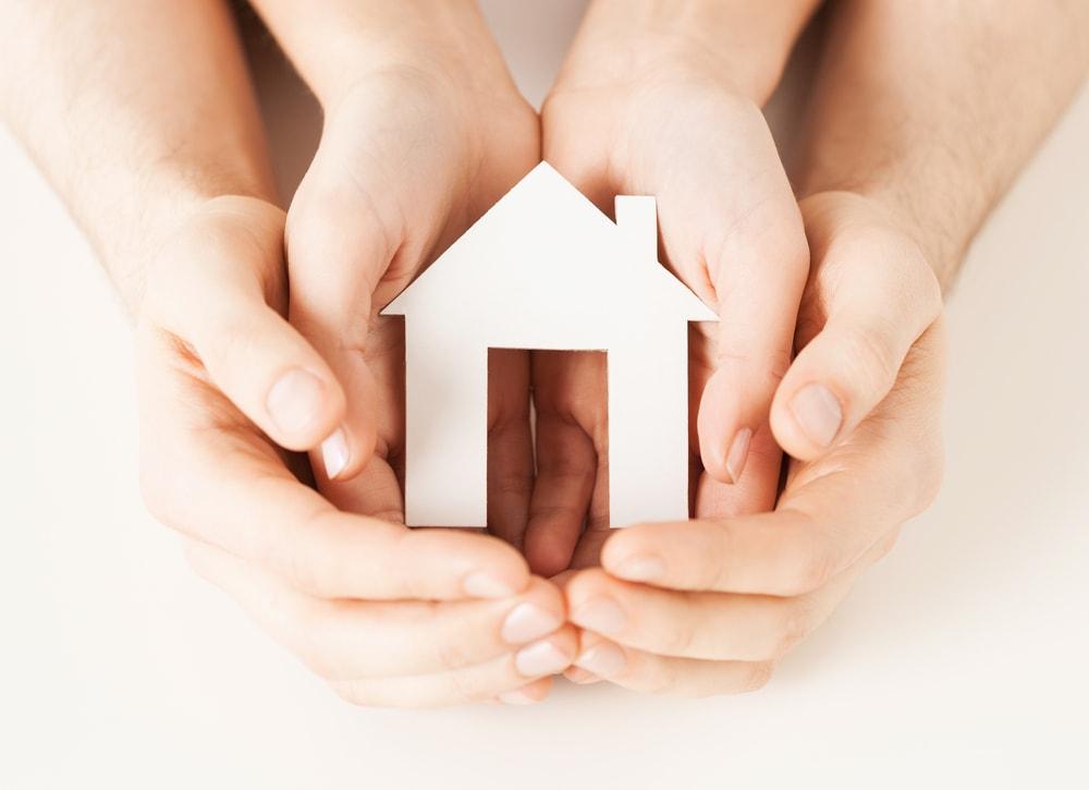 手で家の模型を持つ親子