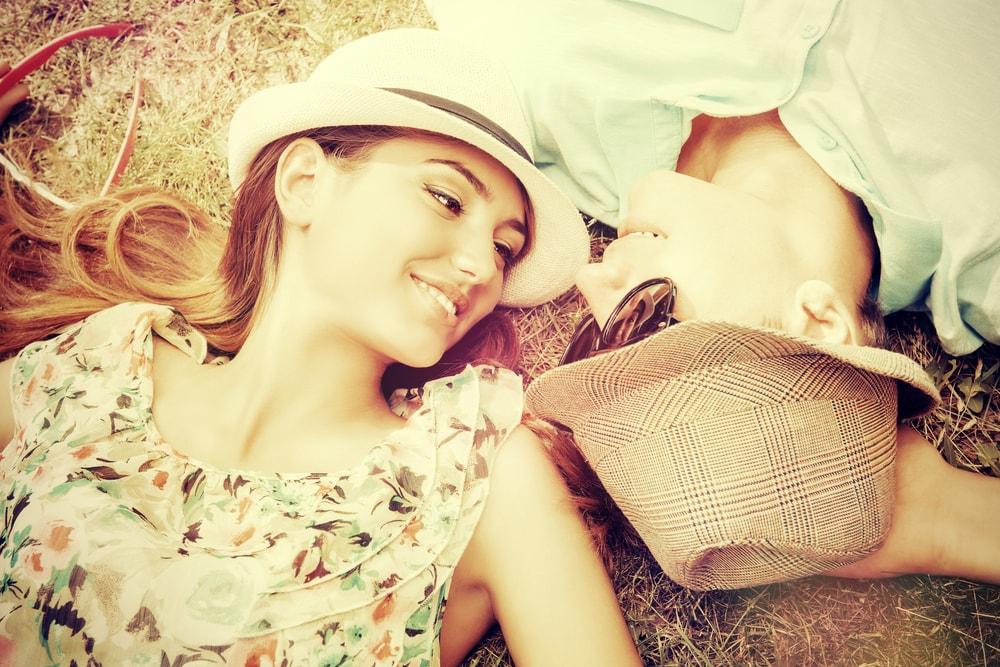 草原に寝転がるカップル