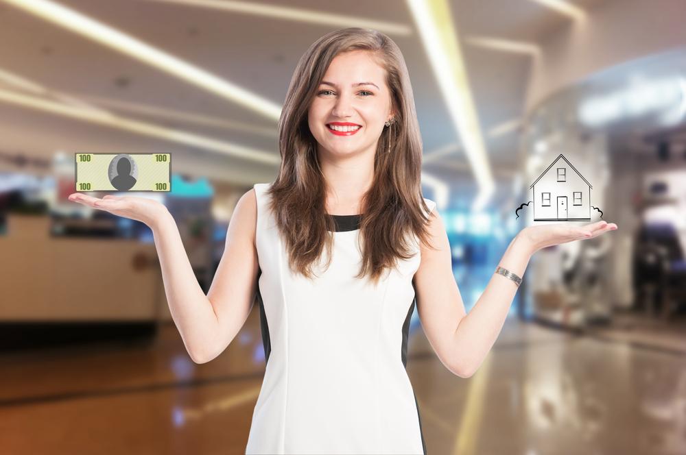 家の模型と札束を持つ女性