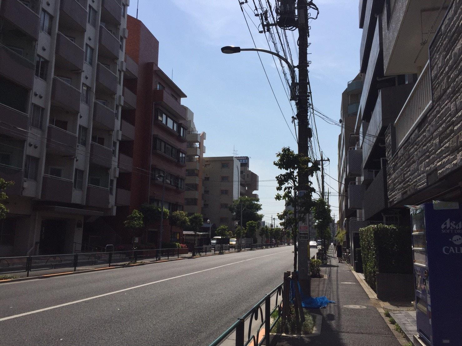 大型のマンションが建っている大通り沿いの風景