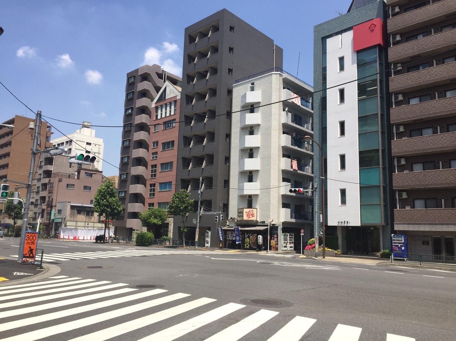 大通り沿いに単身向けマンションが多く建っている風景
