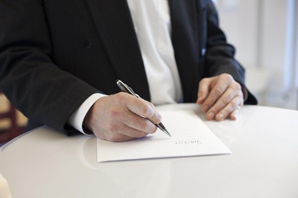 契約書を書いている男性の手