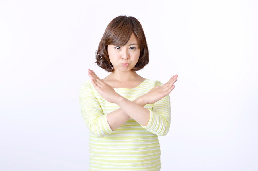 手でバツ印を作る女性