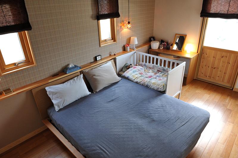 夫婦のベッド横にベビーベッドを置いている例