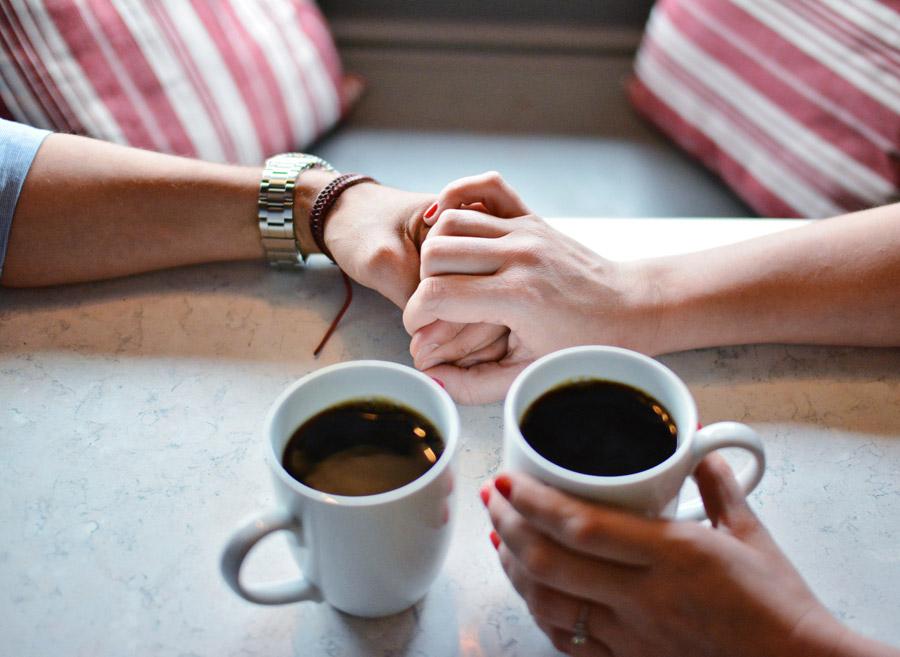 コーヒーカップと手を繋ぐカップル-min