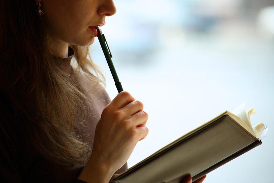 ノートを見て悩む女性