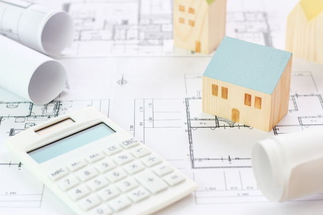 家の置物と図面と電卓