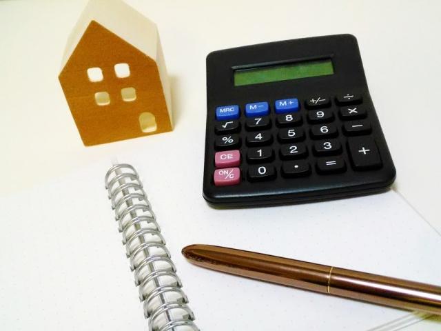 家の置物と電卓とノート