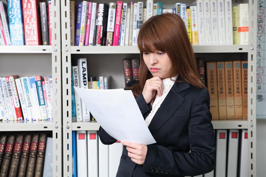 書類を見て悩む女性