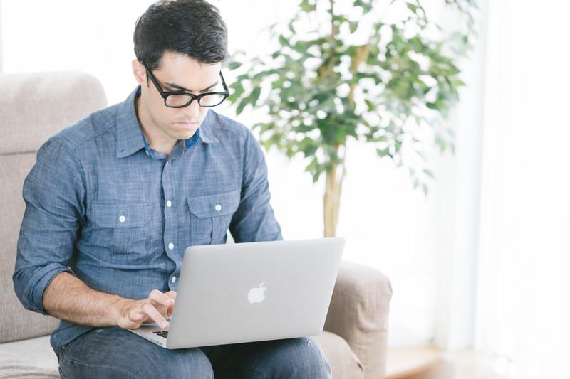 PCを操作するメガネをかけた男性
