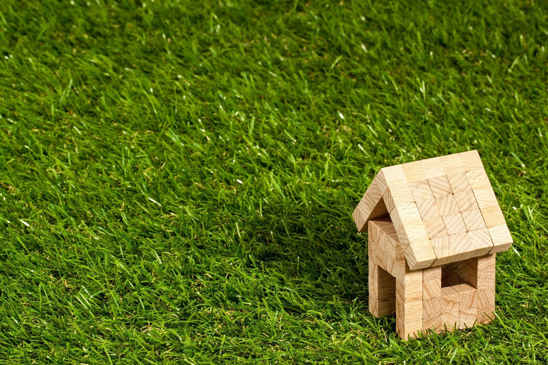 芝生の上にある家型の木製おもちゃ