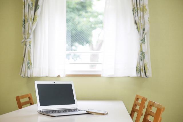窓から差し込む光とノートパソコン