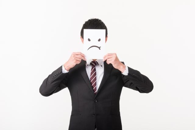 口を結んだイラストで顔を隠す男