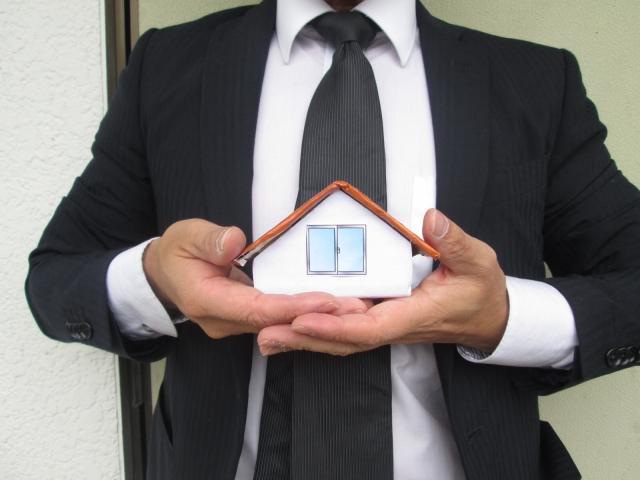 家の模型を持つサラリーマン