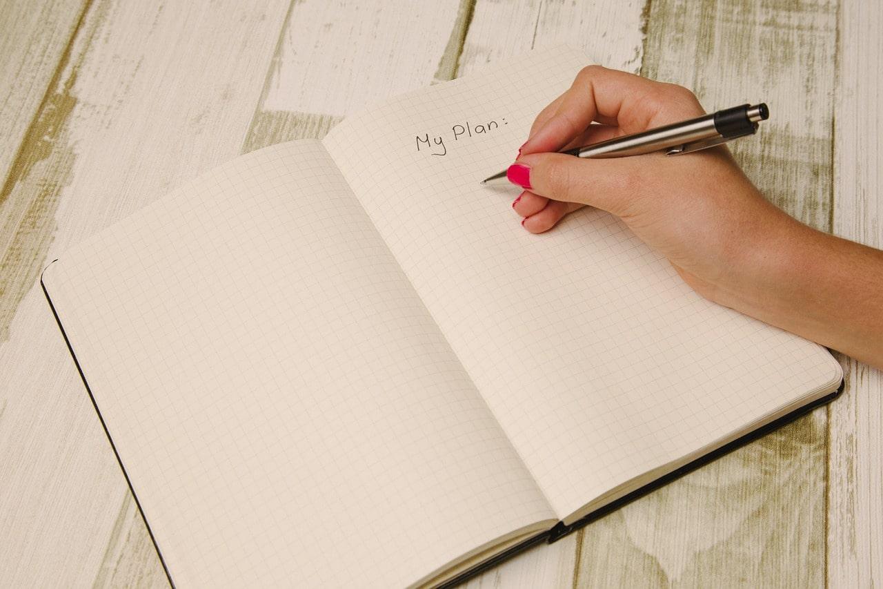 メモ帳に書き込む女性の手