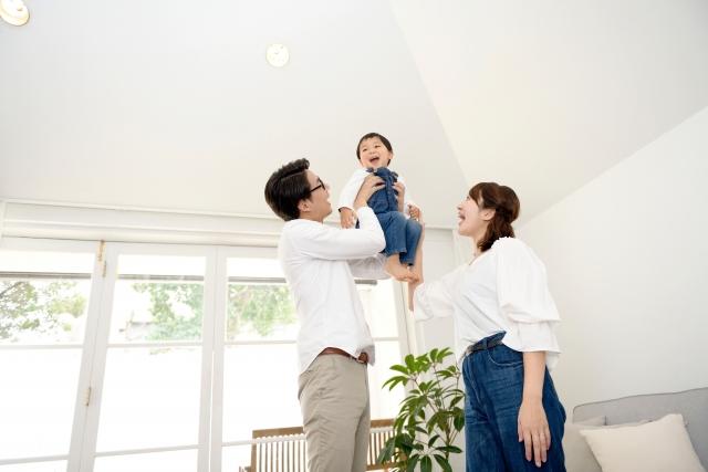 白いお部屋で子どもを抱っこする夫婦