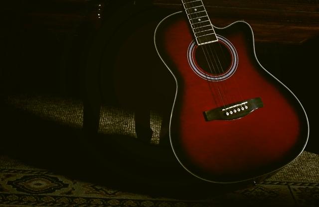 暗めの部屋に置かれたアコースティックギター