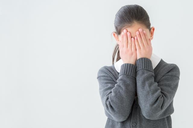 顔を隠して泣く女子高校生