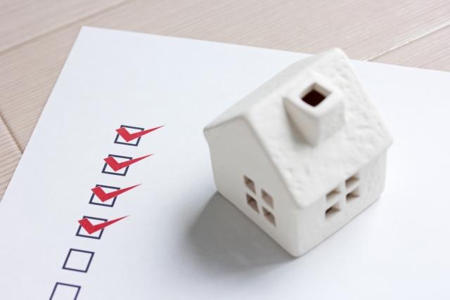 チェックリストの上に置かれた家の模型