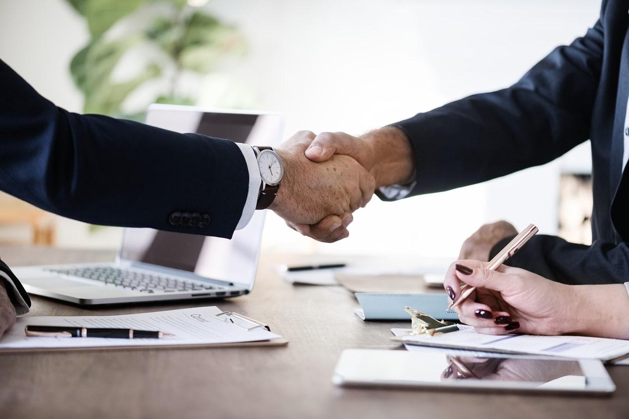 デスクの上で握手するビジネスマン