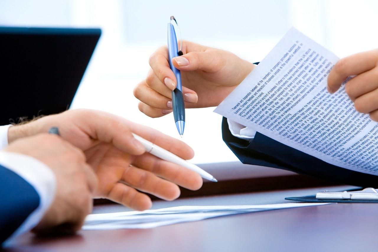 机上の書類をもとに調べる会社員