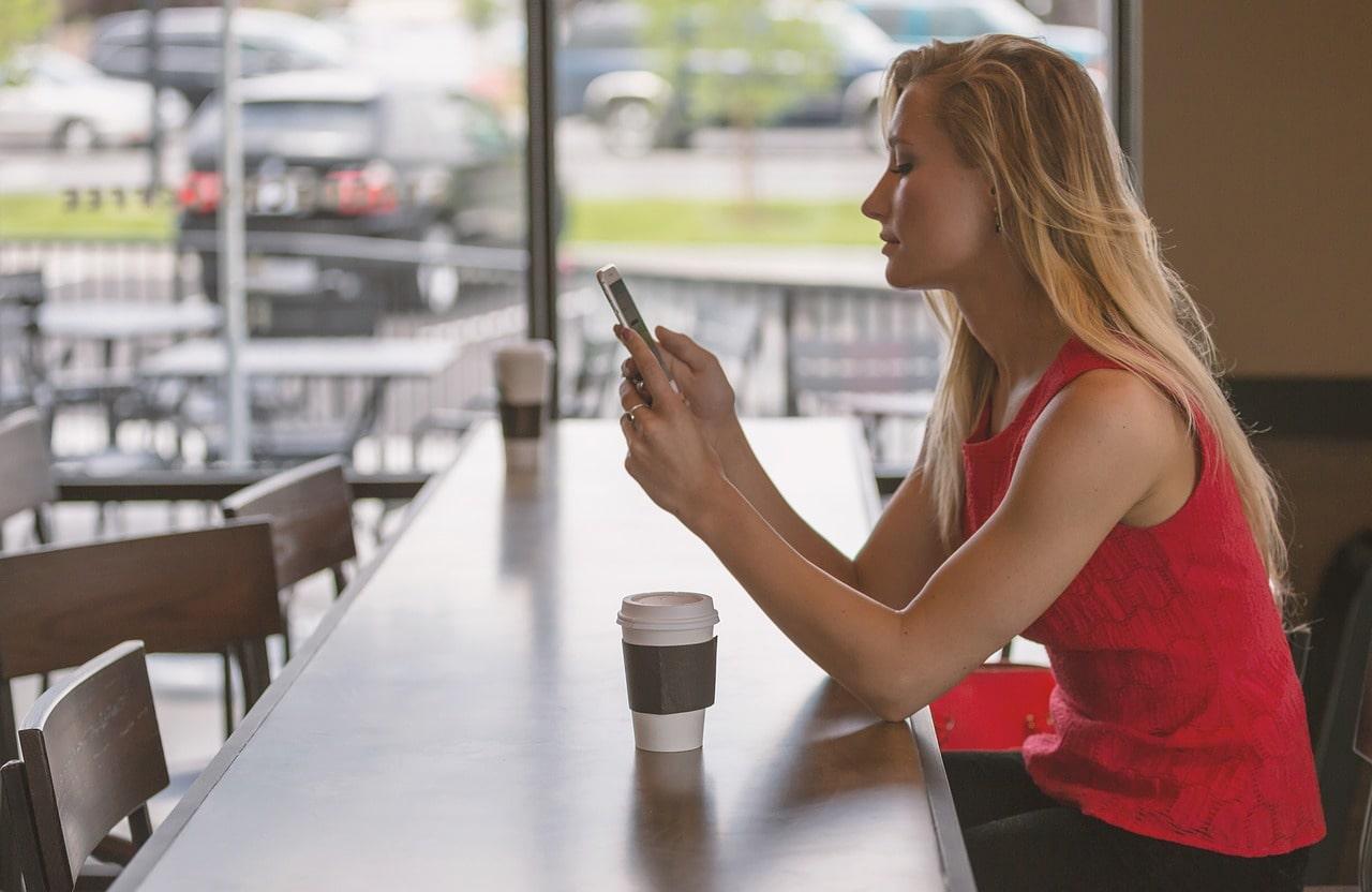 喫茶店のカウンターで電話をかけようとしている女性