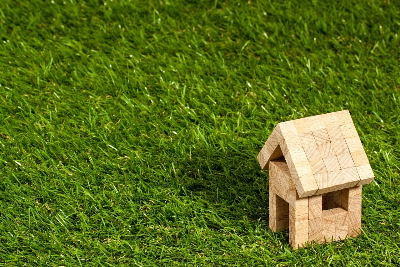 芝生に置かれた木製の家型おもちゃ