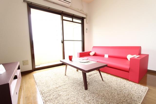 ピンクの大きなソファーと白のラグ