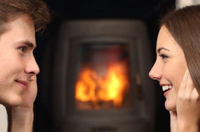 暖炉の前で向かい合うカップル
