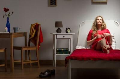 暗い部屋のベッドに寝そべる女性