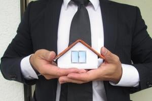 家の模型を持っている営業マン
