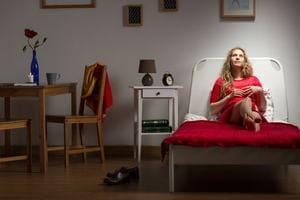 赤いベッドに寝そべる女性