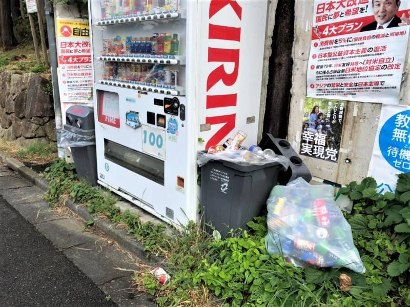 自動販売機とゴミ箱からあふれた空き缶