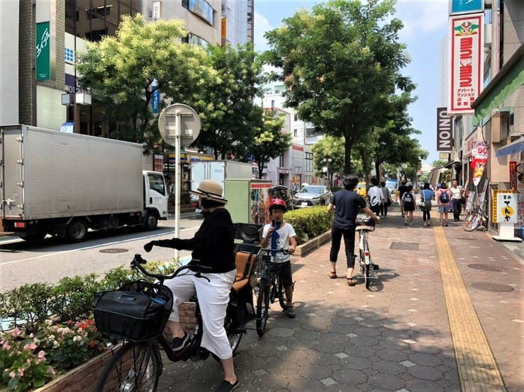 大宮駅の繁華街を自転車で移動する親子