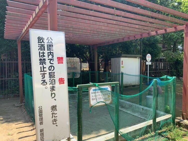 公園の砂場と警告看板