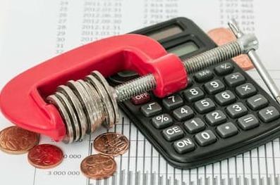 電卓と万力で圧縮されている小銭