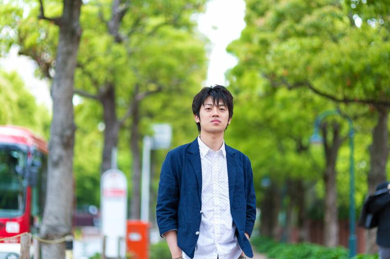 緑の道を歩く青年
