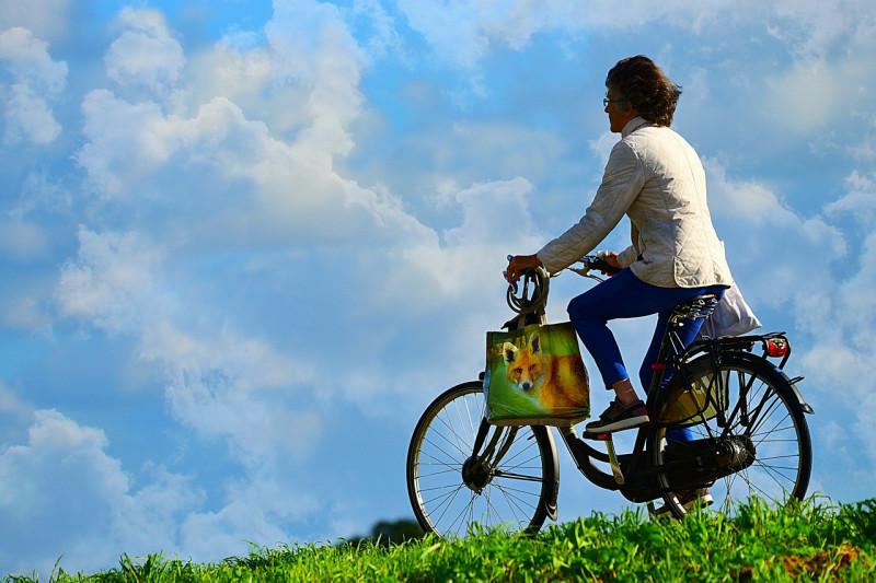 青空をバックに河川敷を走る自転車
