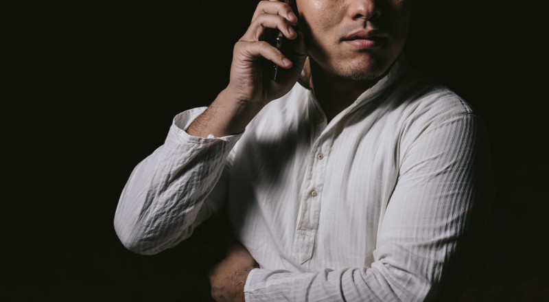 電話で相談する男性