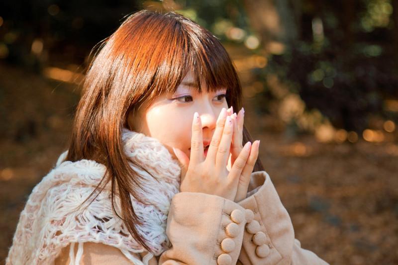 息で手を温めている女性