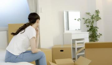 引っ越しの荷造りで悩む女性